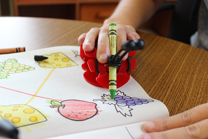 Showing how it works holding a crayon and coloring
